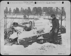 Capt. James R. Lloyd, 124 E. Walnut St., Lancaster, Pa., a 9th AF Air Liaison officer, stands by a German Tiger tank disabled during the battle of the bulge.